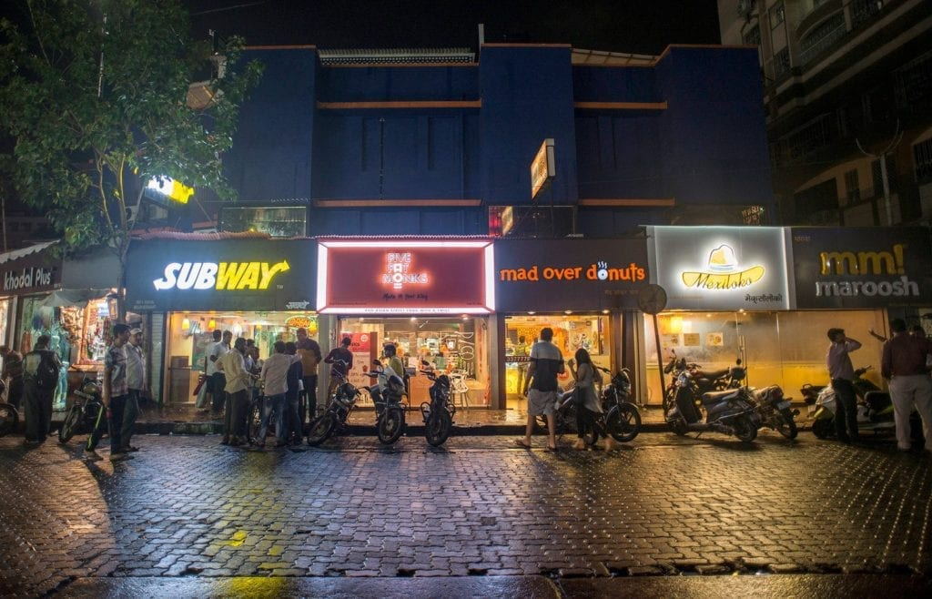 Pedestrians visit fast-food restaurants in Mumbai, India. Rapid urbanization in many developing countries is driving the demand for fast foods and highly processed, packaged foods. Aniruddha Chowhdury/Mint/Hindustan Times via Getty Images